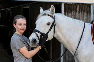 Teenage girl horse rider with a grey horse outside a stable, adjusting the girth and saddle.の写真素材 [FYI02265166]