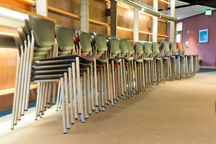 Chairs in an office stacked and lined up prior to a corporate meeting.の写真素材 [FYI02265167]