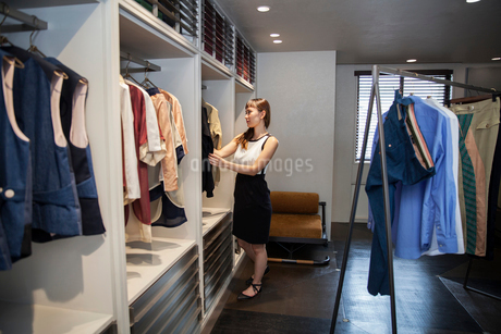 Japanese saleswoman standing in clothing store, looking at clothes rail.の写真素材 [FYI02265174]
