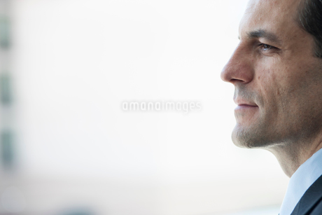 Closeup of a Caucasian businessman looking out the widow of a conference centre lobby.の写真素材 [FYI02265176]