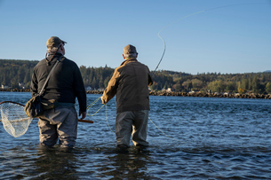 A guide advises his client while fly fishing in salt water for searun coastal cutthroat trout and saの写真素材 [FYI02265177]