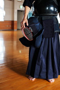Male Japanese Kendo fighter standing in a gym, holding Kendo mask.の写真素材 [FYI02265185]