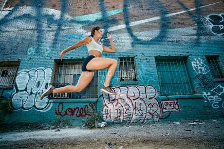 Female athlete running along street past blue building covered in graffiti.の写真素材 [FYI02265187]