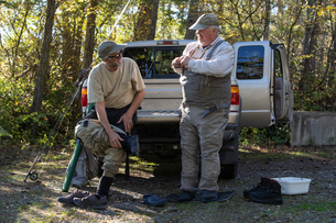 Two Caucasian male fly fishermen enjoy some conversation around a pickup truck while putting on theiの写真素材 [FYI02265192]