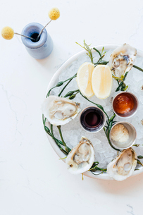 Platter of oysters on ice with lemons and saucesの写真素材 [FYI02265194]