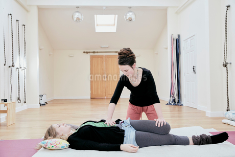 Woman lying down having a Thai massage, a masseur stretching her legs and knee joints.の写真素材 [FYI02265201]