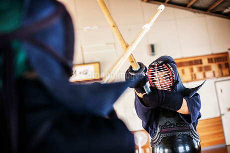 Two Japanese Kendo fighters wearing Kendo masks practicing with wood sword in gym.の写真素材 [FYI02265208]