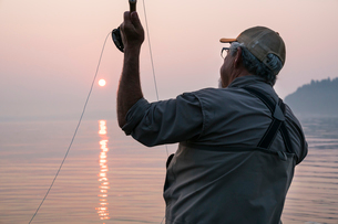Senior Caucasian male fly fishing for salmon and sea run cutthroat trout off the coastの写真素材 [FYI02265209]