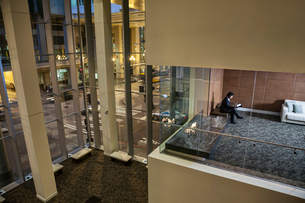 A view looking down into a conference room with a business woman looking at a notebook computerの写真素材 [FYI02265216]