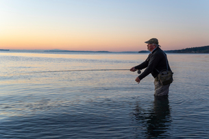 A side view of a fly fisherman at sunrise casting for salmon and searun coastal cutthroat trout fromの写真素材 [FYI02265219]
