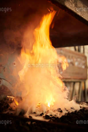 Flames and smoke billowing from a forge fire in a metal workshop.の写真素材 [FYI02265220]