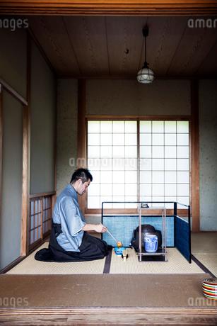 Japanese man wearing traditional kimono kneeling on floor, using a Hishaku, a bamboo ladle, during aの写真素材 [FYI02265225]
