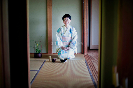 Japanese woman wearing traditional white kimono with blue floral pattern kneeling on tatami mat duriの写真素材 [FYI02265227]
