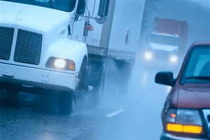 Partial view of large commercial truck driving in hazardous conditions of snow and rain on a freewayの写真素材 [FYI02265233]