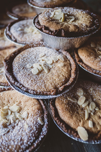 High angle view of freshly baked tarts topped with flaked almonds and icing sugar.の写真素材 [FYI02265250]