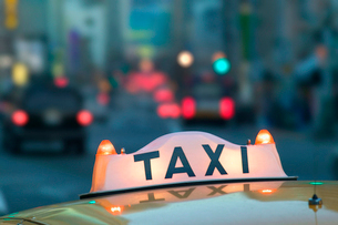 Closeup of a taxi sign on top of a taxi cab in the city at night.の写真素材 [FYI02265252]