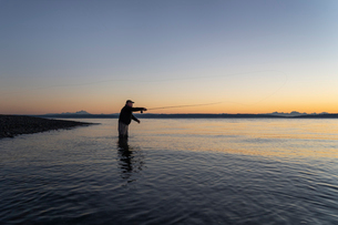 A silhouette view of a fly fisherman casting for salmon and searun coastal cutthroat trout from a saの写真素材 [FYI02265263]