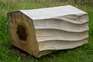 Close up of carved piece of tree trunk with wave pattern lying on grass.の写真素材 [FYI02265269]