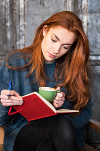Young woman with long red hair sitting at table, holding notebook and cup of coffee.の写真素材 [FYI02265270]