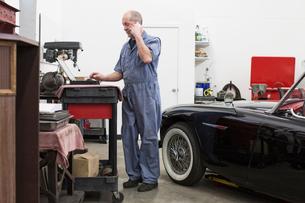 A senior Caucasian male car mechanic working on his laptop computer in his classic car repair shop.の写真素材 [FYI02265273]