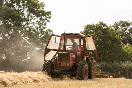 Tractor and straw baler in wheat field, farmer baling straw.の写真素材 [FYI02265282]