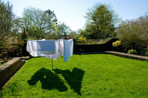 A rotary washing line with laundry drying in the sun on a drying green.の写真素材 [FYI02265284]