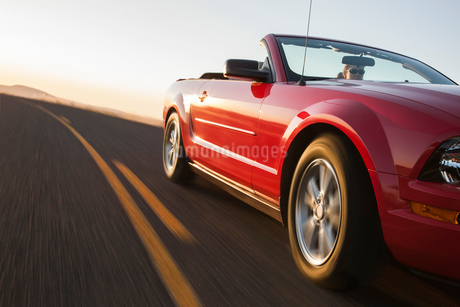 A low angle view of a convertible sports car moving on a highway late in the day.の写真素材 [FYI02265289]