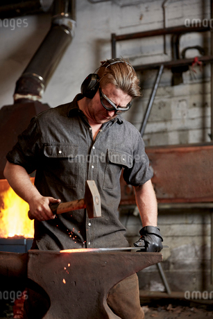 An artisan metal worker in ear protectors using a hammer to shape a red hot piece of metal on an anvの写真素材 [FYI02265301]