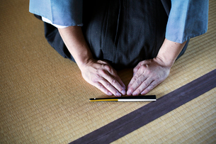 High angle close up of Japanese man kneeling on tatami mat in front of Sensu fan during a tea ceremoの写真素材 [FYI02265302]