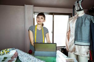 Japanese female fashion designer working in her studio, smiling at camera.の写真素材 [FYI02265305]