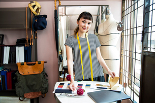 Japanese female fashion designer working in her studio, smiling at camera.の写真素材 [FYI02265315]