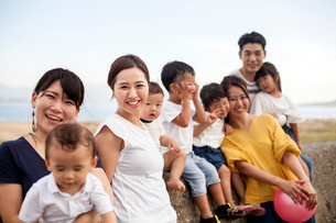 Group portrait of Japanese families with young children on promenade by ocean, smiling at camera.の写真素材 [FYI02265319]