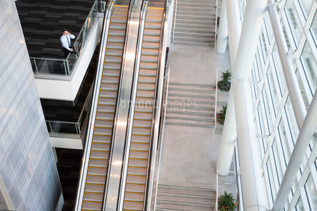 View from above looking down on a businessman using his phone in a conference centre lobby.の写真素材 [FYI02265320]