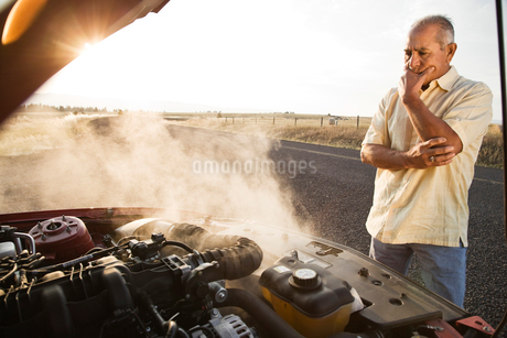 An Hispanic senior man pulled over at the side of the road with engine trouble.の写真素材 [FYI02265325]