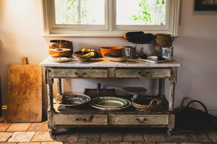 Selection of earthenware bowls and plates on antique court cupboard with drawers.の写真素材 [FYI02265326]