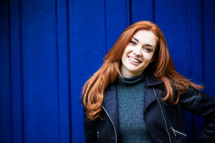 Portrait of smiling young woman with long red hair in front of bright blue door.の写真素材 [FYI02265338]