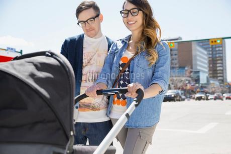 Hipster couple pushing stroller on sunny urban streetの写真素材 [FYI02265340]