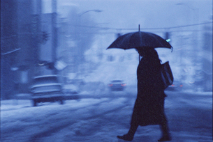 A woman walking across a city street covered in snow and rain in the winter.の写真素材 [FYI02265342]