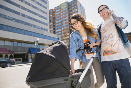 Hipster couple pushing stroller on sunny urban streetの写真素材 [FYI02265346]