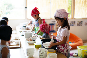 A girl and a boy wearing headscarves standing at a table in a Japanese preschool, serving lunch.の写真素材 [FYI02265352]