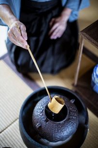 High angle close up of traditional Japanese Tea Ceremony, man using a Hishaku, a bamboo ladle, to poの写真素材 [FYI02265354]