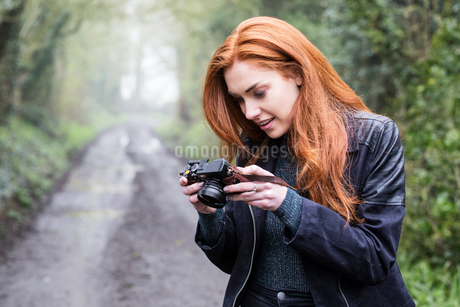 Smiling young woman with long red hair walking along forest path, taking pictures with vintage camerの写真素材 [FYI02265356]