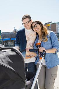 Hipster couple pushing stroller on sunny urban streetの写真素材 [FYI02265359]