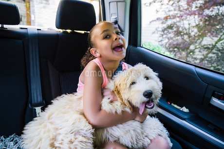 Girl with labradoodle puppy in car making goofy faceの写真素材 [FYI02265373]