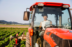 Portrait of Japanese farmer driving red tractor.の写真素材 [FYI02265374]