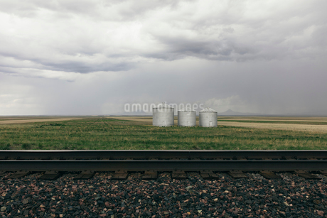 Grain silos and storm clouds over vast farmland and prairie, train tracks in foregroundの写真素材 [FYI02265377]