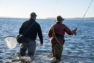 A guide advises his client while fly fishing in salt water for searun coastal cutthroat trout and saの写真素材 [FYI02265380]