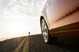 An automobile approaching a person standing on the side of a road.の写真素材 [FYI02265386]