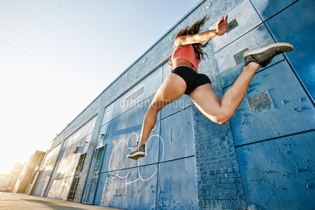 Low angle view of female athlete running along sidewalk past blue building covered in graffiti.の写真素材 [FYI02265389]