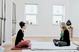 Two women sitting crossed legged facing each other in an exercise studioの写真素材 [FYI02265391]